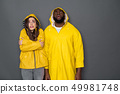Waist up of frustrated interracial couple wearing yellow raincoats against gray background 49981748