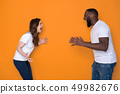 Side view of screaming interracial couple in white T-shirts posing for camera 49982676
