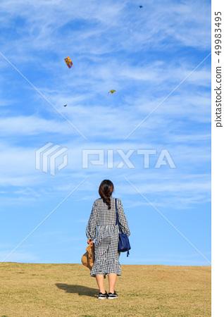 파란하늘을 올려다보고 있는 임신한 여성 49983495