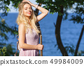 Woman playing acoustic guitar in park 49984009
