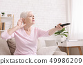 Senior woman cupping her hand behind ear to hear better 49986209