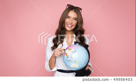 Travel concept. Woman tourist holding globe and pointing on it 49986483