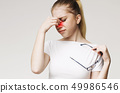 Tired woman suffering from eye pain, massaging nose 49986546