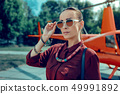 Serious appealing woman taking on big sunglasses while having jewelry 49991892