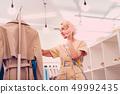Woman choosing clothes while having a phone conversation 49992435