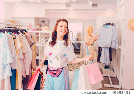 Smiling woman buying a lot of things while doing shopping 49992481