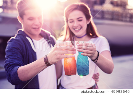 Laughing happy young couple observing glass bottles with refreshing drinks 49992646
