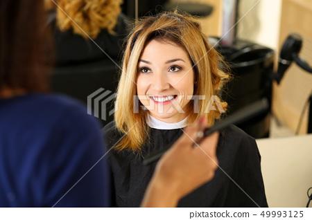 Female hairdresser hands holding comb picking new hairdo 49993125
