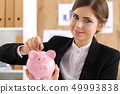 Happy smiling beautiful businesswoman and piggybank 49993838