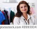Mature smiling female fashion designer standing in workshop portrait 49993934