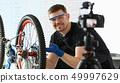 Smiling Man Repairing Mountain Cycle at Workshop 49997629