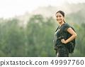 The woman hiker backpacker in meadow. 49997760