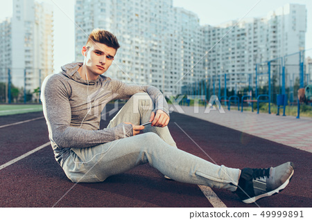 Young handsome guy has a break on running track in the morning on stadium. He wears gray sport suit 49999891