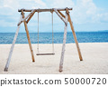 Wooden swing on the beach and Blue Ocean Sea Water 50000720
