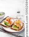 Tasty toasts with avocado, radish and salmon. 50002684