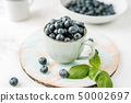 Fresh blueberries in a cup on white background 50002697