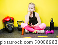 Young child girl with mobile phone sitting on the floor near the dumbbells, boxing gloves and a 50008983