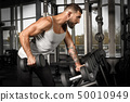 Bodybuilding. Bearded man exercising at gym with dumbbell concentrated side view 50010949