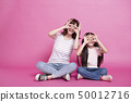 happy mother and daughter holding fingers near 50012716