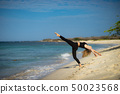 Blond young girl wearing black tights doing dancing poses on the beach. Summer day and happy holiday 50023568