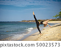 Blond young girl wearing black tights doing dancing poses on the beach. Summer day and happy holiday 50023573