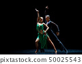 Couple of dancers performing on isolated black background 50025543