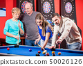 Young and mature couple playing billiard 50026126