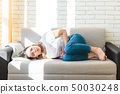 Beautiful young woman suffering from abdominal pain while laying on sofa at home 50030248