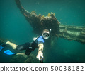 Free diver taking selfie with sunken ship on background 50038182