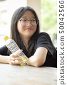 asian teenager smiling face holding pastic bottle 50042566
