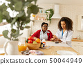 Woman sitting at the table while private nurse taking the blood counts 50044949