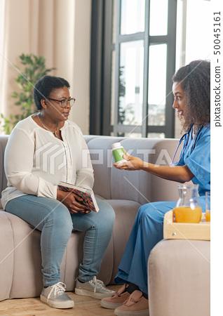Aged woman feeling thankful to nurse bringing the pills 50045161
