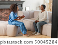 Aged lady sitting on sofa and answering the questions of private nurse 50045284