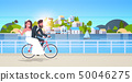 just married man woman riding bicycle romantic couple bride and groom cycling bike having fun 50046275