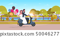 just married couple riding motor scooter with colorful balloons bride and groom having fun wedding 50046277