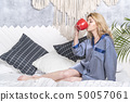 woman drinking tea from a red cup 50057061