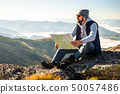 Hipster young man holding in hands and looking on map on mountain background 50057486
