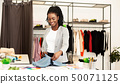 Young fashion designer working with fabric, choosing color 50071125