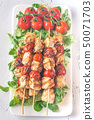 Grilled chicken skewers on the white plate 50071703
