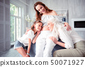 Pregnant woman hugging mother and daughter listening to her tummy 50071927