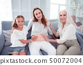 Pregnant woman sitting in the middle between mother and daughter 50072004