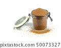 Brown cane sugar in glass jar isolated on white 50073327