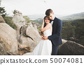Happy wedding couple kissing and hugging near a high cliff 50074081