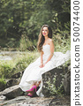 Beautiful happy bride outdoors in a forest with rocks. Wedding perfect day 50074400