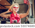 Delighted joyful aged woman posing for a selfie 50074689