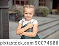 Happy little schoolgirl with book going back to school outdoor. 50074988