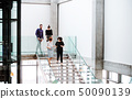 Group of young businesspeople walking down the stairs, talking. 50090139