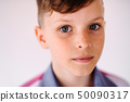 Close-up portrait of small boy standing against white background. 50090317