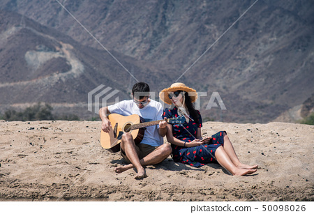 Couple singing and playing guitar buy the beach 50098026