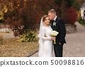 Stylish couple wolking in the park at their wedding day. Happy newlyweds outside in autumn weather 50098816